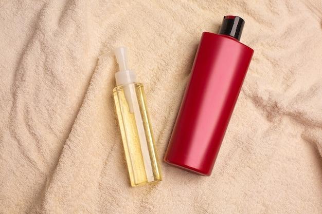 バスルームのしわくちゃのタオルの上に横たわるヘアシャンプーとミセルフェイスオイル。コピースペース