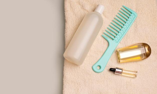 バスルームのしわくちゃのタオルの上に横たわるヘアシャンプー、くし、活力を与える血清。コピースペース