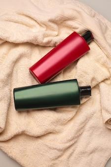ヘアシャンプー、バスルームのベージュのバスタオルの上に横たわる保湿コンディショナー。コピースペース