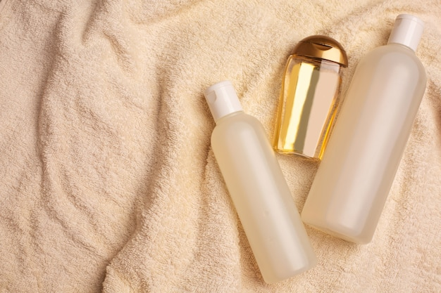 バスルームのしわくちゃのタオルの上に横たわるヘアシャンプー、オイル、活性化マスク。コピースペース