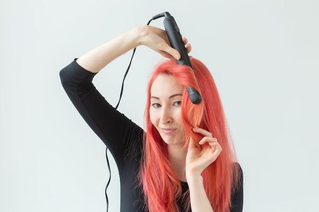 Прическа, парикмахер и люди концепция - стильная рыжеволосая женщина с щипцами для завивки на белом