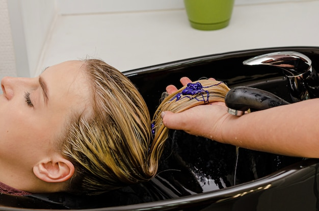 Hair stylist applying coloring purple shampoo after hair dyeing.