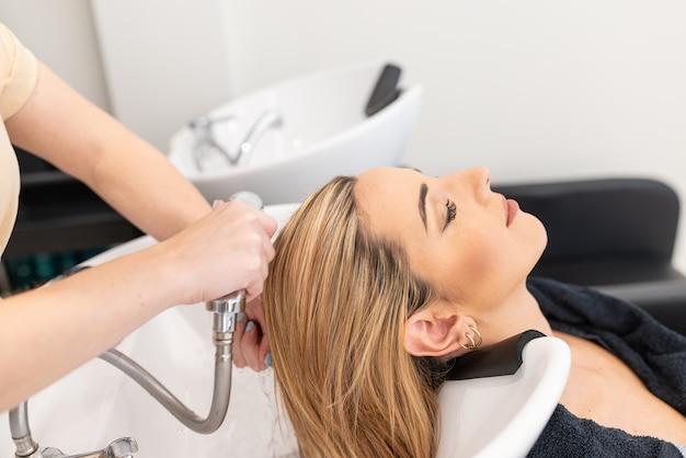 Парикмахер на работе - парикмахер, моющий светлые воздушные волосы клиентке кавказской женщины с закрытыми глазами. выборочный фокус