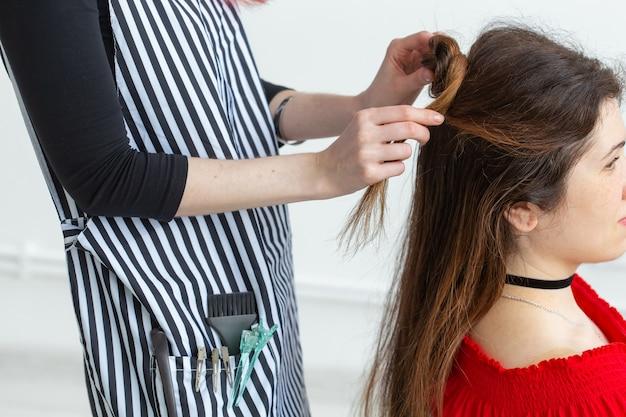 ヘアスタイリスト、美容と人々のコンセプト-若い女性を着色する女性の美容師。