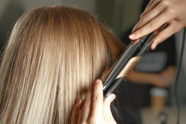Парикмахер делает локоны утюжком молодой блондинке в салоне красоты. снимок крупным планом