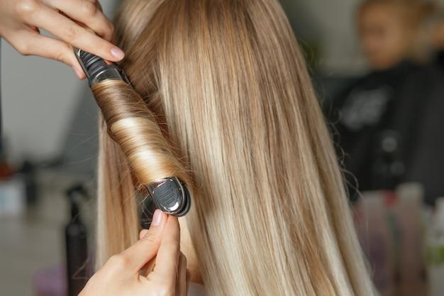 Парикмахер делает локоны с помощью утюжка для волос клиентке в салоне красоты. снимок крупным планом