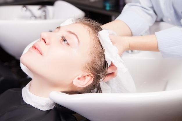 Парикмахер сушит волосы женщины полотенцем в салоне