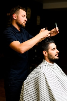 Hair stylist giving man a new hairstyle