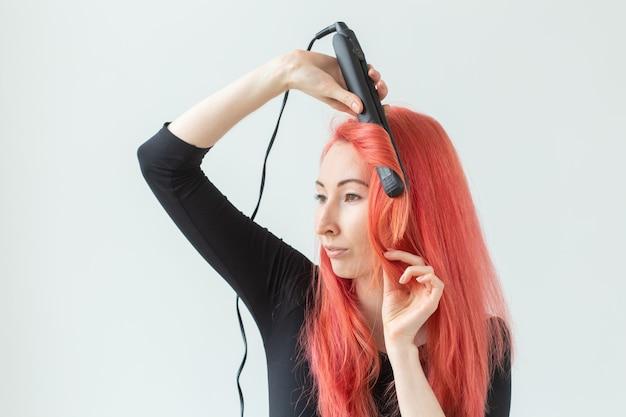 ヘアスタイリスト、美容師、人々のコンセプト-白い背景の上にヘアアイロンを保持している色の髪を持つ若い女性。