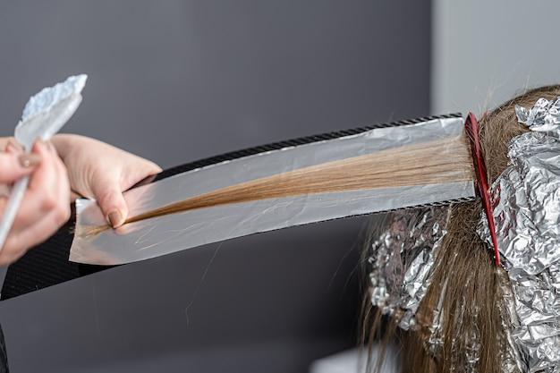 헤어 스타일리스트는 얇은 가닥에 부푼 트를 만들고 shatush 기술을 사용하여 표백 파우더를 적용합니다.