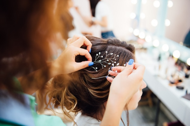 Hair stylist makes the bride a wedding hairstyle