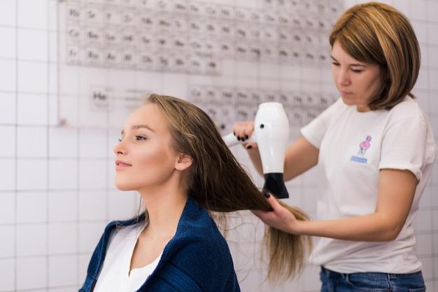 ブルネットの女性にリングレットを作るヘアスタイリスト
