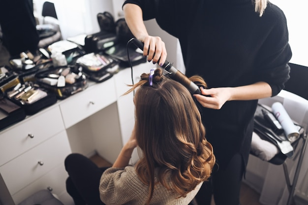 Hair stylist prepares beautiful young woman for event, makes curls hairstyle with a curling iron for client in beauty salon