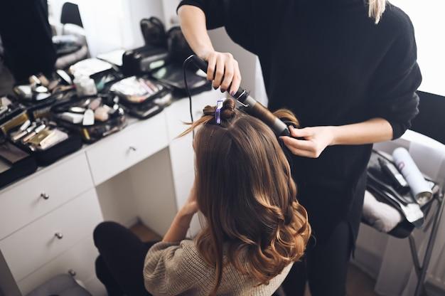 ヘアスタイリストはイベントのために美しい若い女性を準備し、美容院のクライアントのためにヘアアイロンでカールヘアスタイルを作ります