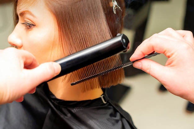 Hair stylist's hands straightening short hair of young brunette woman with flat iron and comb in a beauty salon