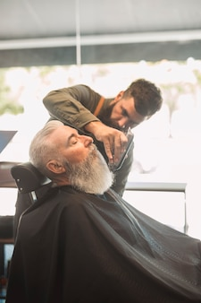 Hair stylist trimming beard to aged male in salon