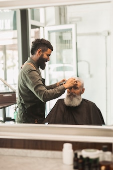 Hair stylist trimming hair to aged male in salon