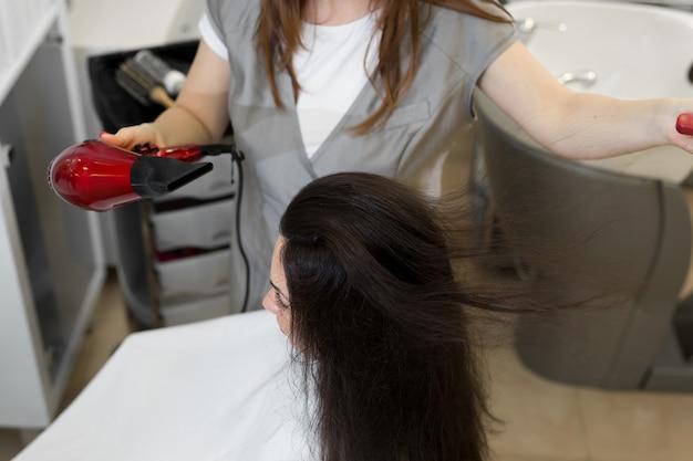 헤어 스타일리스트는 살롱에서 여자 헤어 스타일에서 작동합니다. 헤어 드라이어와 둥근 브러시로 긴 갈색 머리 건조