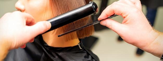 Парикмахеры выпрямляют короткие волосы молодой брюнетки с помощью утюжка и расчесывают волосы ...