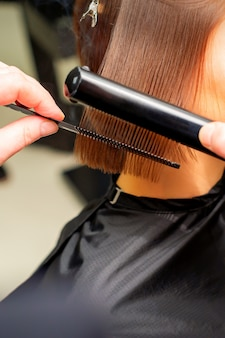 Руки стилистов выпрямляют короткие волосы молодой брюнетки с утюгом и расческой в салоне красоты