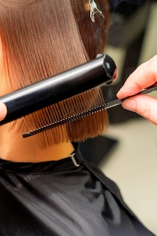 Hair stylists hands straightening short hair of young brunette woman with flat iron and comb in a beauty salon