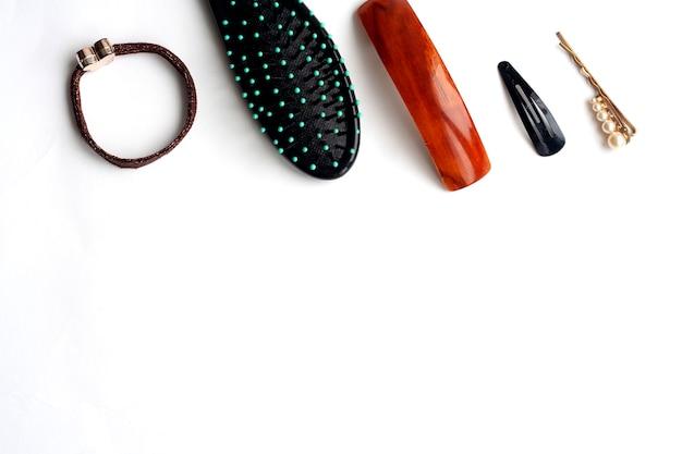 白い背景、フラットレイ、コピースペースのヘア用品、くし、アクセサリー