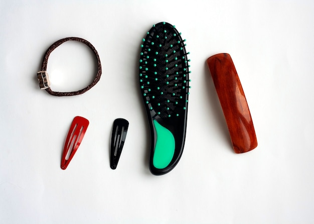 白い背景の上のヘア用品、くし、アクセサリー、フラットレイ