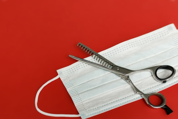 Hair thinning scissors and medical mask on a red background