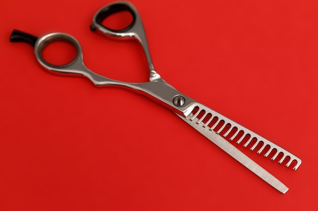 Hair thinning scissors on a red background.