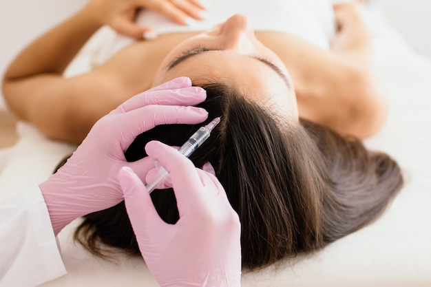 Hair treatment in cosmetology using mesotherapy, injection to the head