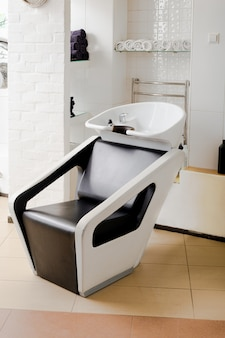 Hair wash sink for washing hair in beauty salon or barber shop, shampoos, towels. hairdresser stylist work space. beauty salon interior.