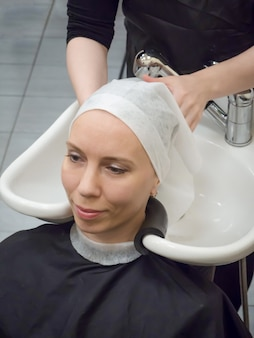 Hair washing in the salon. drying the hair with a towel before the hair restoration procedure.