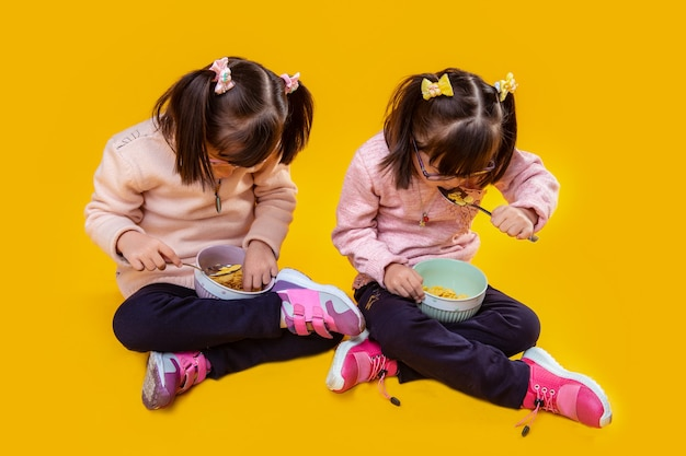 Hair with bangs. concentrated little sisters eating milk with cereals from deep bowls while sitting on bare floor