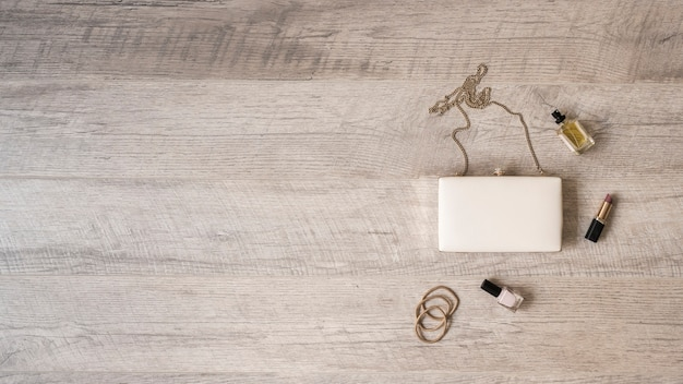 Hairbands; perfume bottle; lipstick and nail varnish with white clutch on wooden textured backdrop