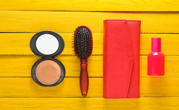 Hairbrush, mirror, purse, bottle of perfume. trend accessories on a yellow wooden background. top view.