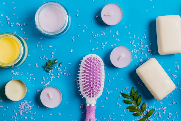 Hairbrush; soap and cream with pink salt spread on blue background