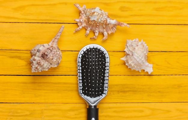 黄色い木製の貝殻のヘアブラシ
