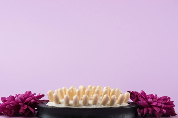 Hairbrush with two pink flowers against purple backdrop