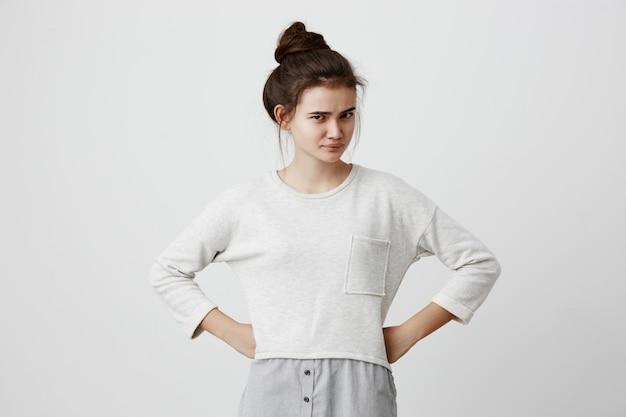 Hairbunと楕円形の顔、暗い目、ゆるいカジュアルセーターを着ている、眉を眉をひそめている、腕を腰に当て立っている、親の言葉に不満を持っているイライラして不満のあるブルネットの女性