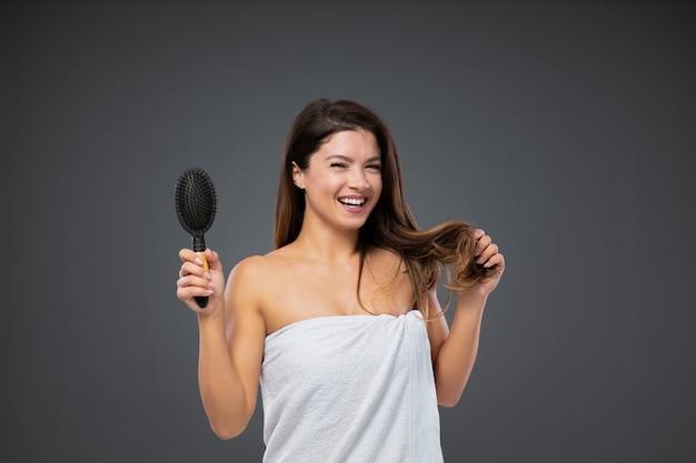 ヘアケアと美容。彼女の体の周りに白いタオルに包まれた美しいブルネットは、灰色の壁の前に立って、シャワーを浴びた後、ヘアブラシを使用します。自然の美しさと女性らしさ、縮毛矯正