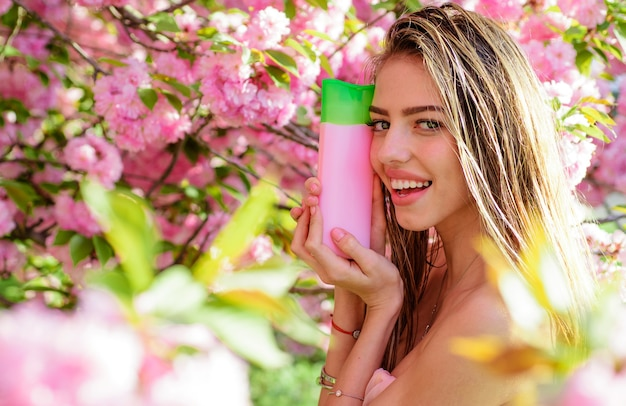 Haircare, beautiful smiling woman with shampoo or conditioner, nature herbal cosmetic for hair.