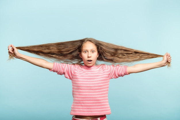 Haircare and styling for kids. shocked adolescent girl holding her long wavy hair.