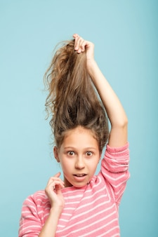 Haircare and styling for kids. surprised adolescent girl holding up her messy hair.
