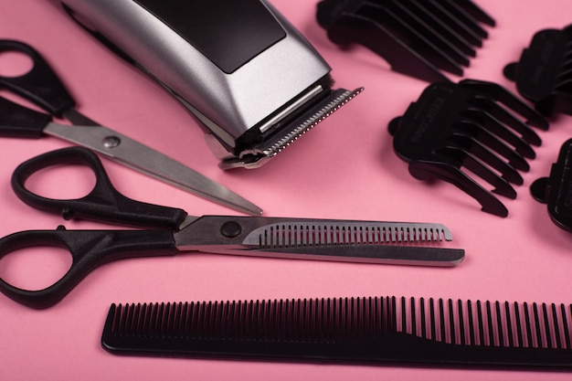 Haircut accessories, barber tools on a pink background