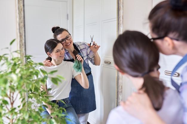 Стрижка дома, мама стрижет дочери волосы, женщина стрижет нездоровые окрашенные волосы, девочка-подросток довольна новой стрижкой