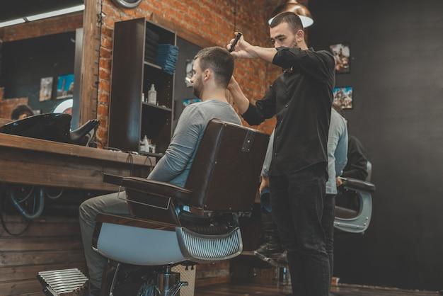 미용사의 이발. 이발사는 고객의 머리에 머리카락을 잘라