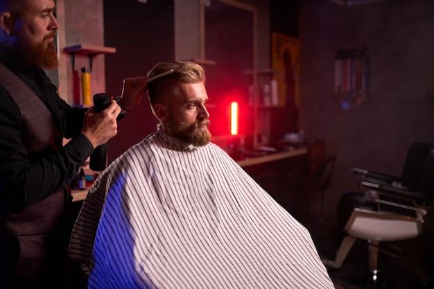 Стрижка в парикмахерской, в салоне красоты. мужчина-парикмахер подстригает красивого молодого клиента волосы на голове