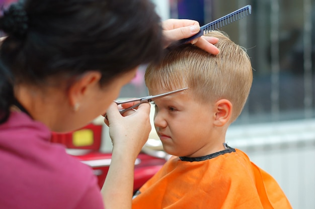 Haircut of a little boy in a children's hairdressing salon