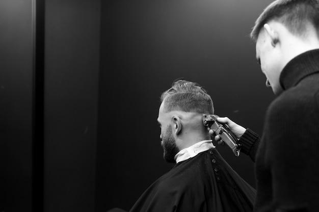 散髪の男性タイプライターのクローズアップ。床屋が男を切る。