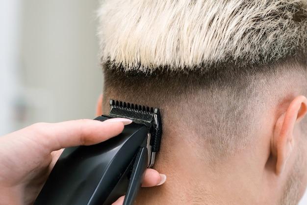 理髪店サロン、男性と男の子のための理髪店のコンセプトの肘掛け椅子にバリカンと金髪の若い男のヘアカットプロセス